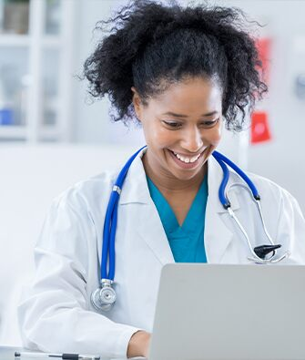 Black female doctor working on computer